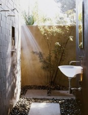 a simple outdoor shower with pebbles and tiles on the ground, greenery and a sink