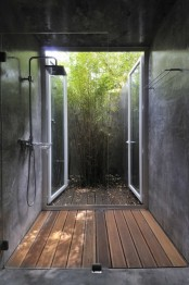 an indoor shower that can be opened to outdoors and fresh greenery growing here