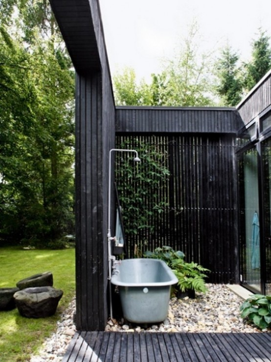a moody outdoor bathroom with black wooden plank walls, a blue bathtub and pebbles on the wall
