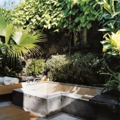 a refined outdoor bathroom with a concrete bathtub, a bench with towels and greenery