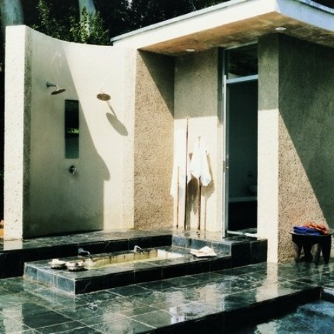 a simple contemporary bathroom outdoors with a shower and a built in bathtub all clad with green tiles