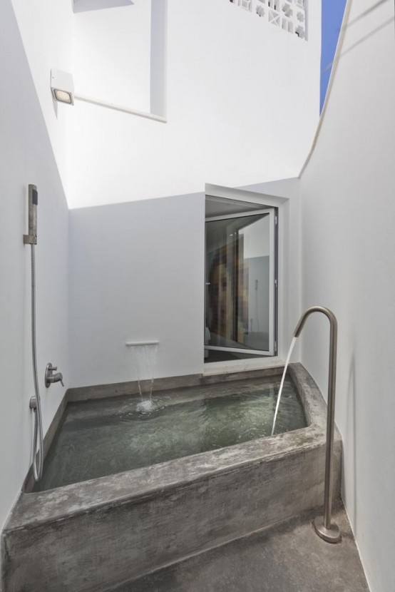 a minimalist outdoor bathroom with a built-in bathtub and simple white walls