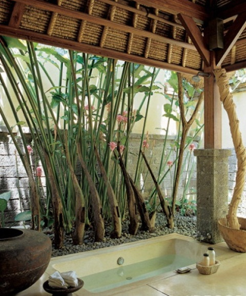 a zen like outdoor bathroom with a built in tub, pebbles, vases and living trees and greenery