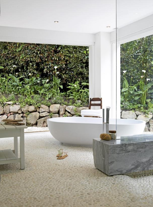 a contemporary outdoor bathroom with an oval tub, a marble bench and wooden tables