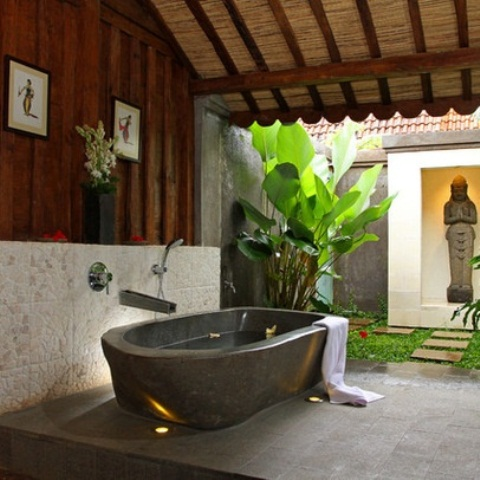 a zen inspired outdoor bathroom with lots of greenery, a stone tub and a statue