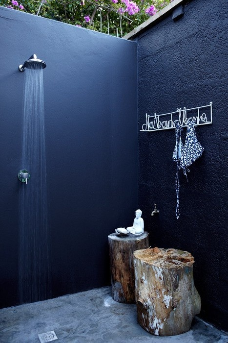 a Nordic outdoor shower done with black walls, a stone floor and a stump as a table for accessories
