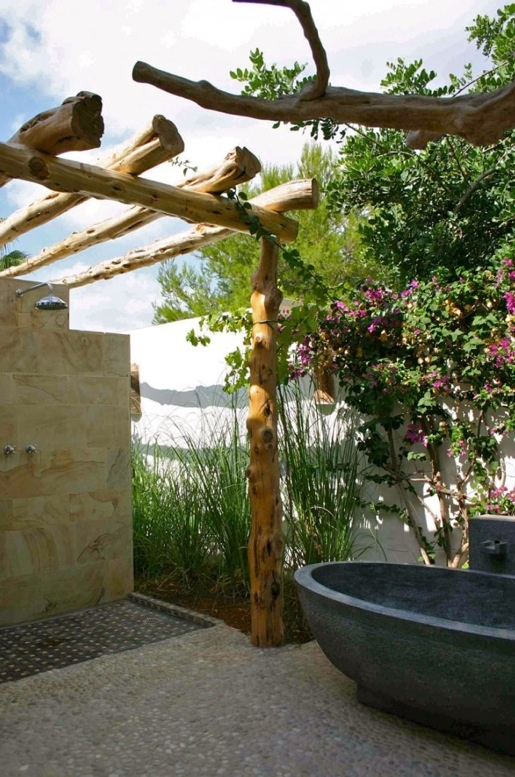 a rustic outdoor bathroom with a stone tub, a tile clad wall and floor and beams