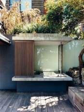 an outdoor bathroom with a built-in concrete bathtub that can be completely hidden