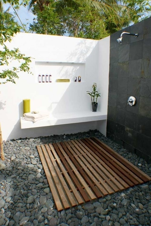 a minimalist outdoor shower with a pallet floor, pebbles, black and white walls and built-in shelves