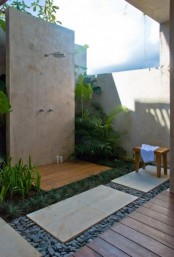 a welcoming outdoor shower with stone tiles, pebbles, tropical greenery and accessories
