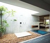 a contemporary outdoor shower with a concrete wall, pebbles and greenery