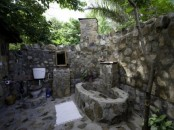 a rustic outdoor bathroom completely done with stone and a stone bathtub