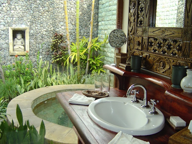 an Asian outdoor bathroom oasis with a large tub pool, a sink, an inlay mirror and much greenery