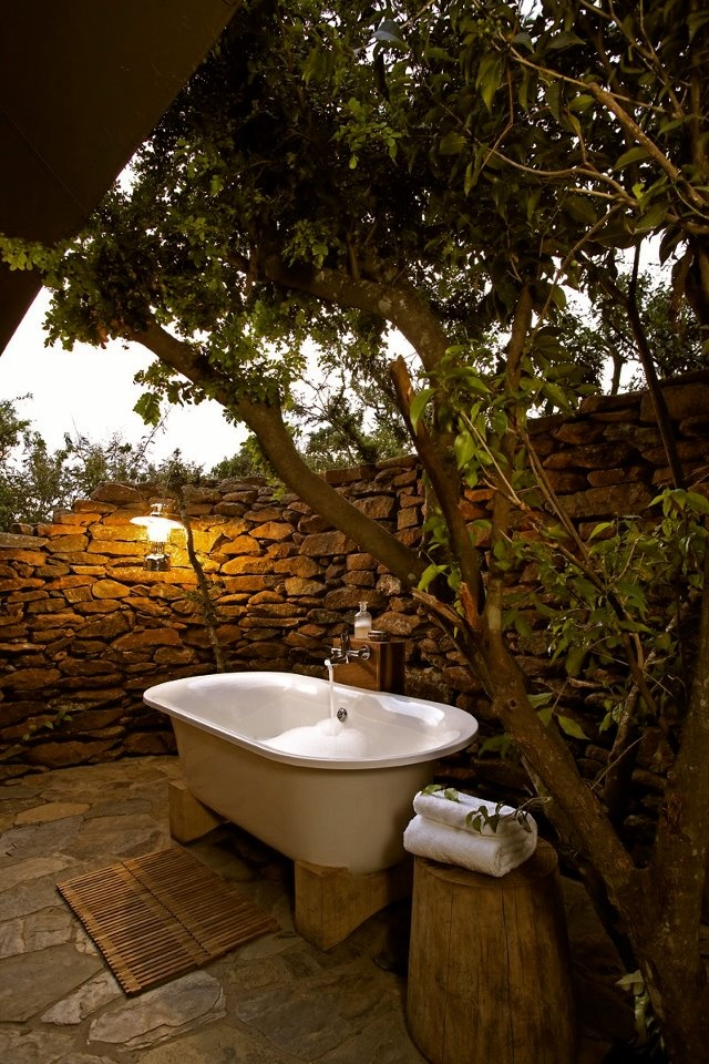 a rustic outdoor bathroom with a stone wall, a tub on stands, stumps as side tables and living trees