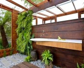 a contemporary outdoor shower space wiht a livign wall, pebbles and a floating sink