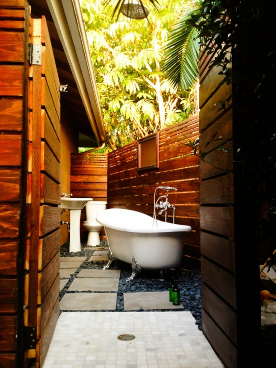 a small yet inviting outdoor bathroom and toilet in one, with dark pebbles on the floor