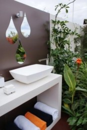 a small modern bathroom nook with a floating vanity, a sink and drop-shaped mirrors