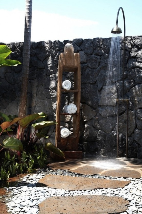a rough outdoor shower with stone walls, pebble floors, planted greenery and a towel shelf