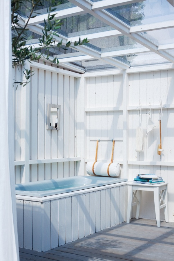 a seaside inspired outdoor bathroom done with beadboards, a blue tub and some accessories plus blue towels