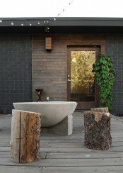 a rough outdoor bathroom space with a concrete tub and several stumps as side tables