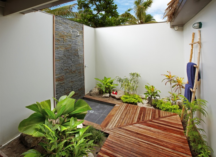 a welcoming outdoor shower nook with a wooden floor, a stone clad wall and much greenery planted here