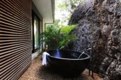 a tropical outdoor bathroom with a stone wall, a metal bathtub and potted greenery