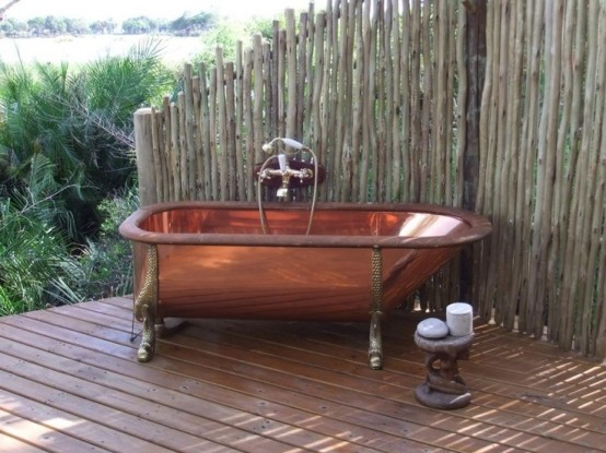 a vintage-inspired outdoor bathroom nook with a copper tub and a wrought side table