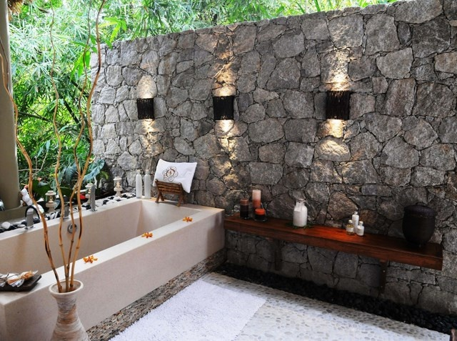 a natural space with a stone wall, a large bathtub, a shelf and built in features