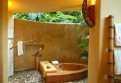 a bathroom with no roof, a stone wall and a concrete sinken bathtub plus greenery