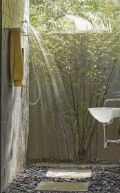 a simple outdoor shower with brick walls, pebbles on the floor, planted greenery and a sink