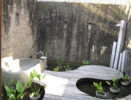a modern and inspiring outdoor bathroom with a wooden floor, a stone tub and potted plants