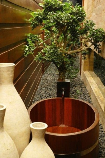 an outdoor Japanese bathroom with a wooden soak tub, a planted tree and vases