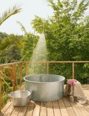 a rustic outdoor bathroom with a metal bathtub and some smaller tubs for storage