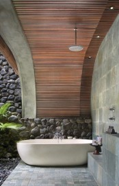 a contemporary outdoor bathroom with an oval tub, tiles and a stone wall