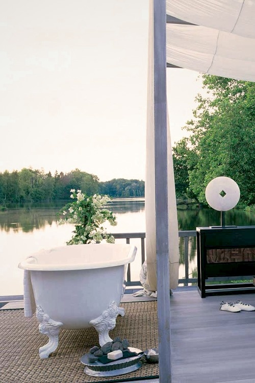 a refined outdoor bathroom with a white bathtub, potted flowers and a rug for coziness