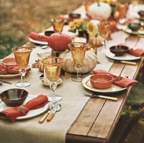 a simple Thanksgiving table with a burlap table runner, red napkins, amber glasses, pumpkins on wood slices