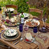 a colorful table runner, colorful glasses, woven placemats, bright candleholders for a bold Thanksgiving party tablescape