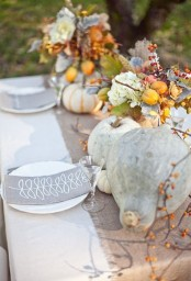 a pale Thanksgiving tablescape with a burlap table runner, grey napkins, grey pumpkins, a floral centerpiece with fruits