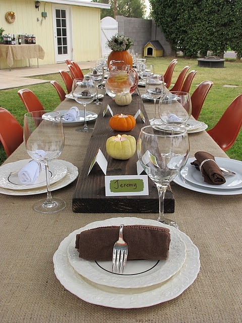 a bright tablescape with a wooden table runner, pumpkin candleholders, a pumpkin vase with blooms