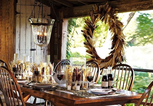 a rustic Thanksgiving tablescape with corn cobs, herbs and a matching wreath hanging next to the table and candles