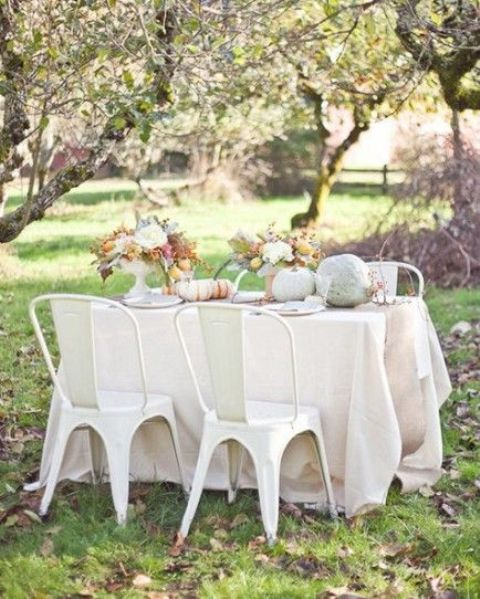 a pale tablescape with neutral heirloom pumpkins and neutral bloom centerpieces for Thanksgiving