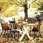 a rustic Thanksgiving table with a stand with pumpkins, fall leaves and vintage chairs with plaid pillows