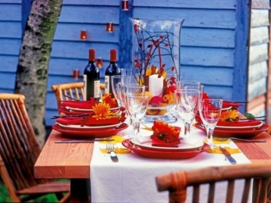 a bold Thanksgiving table setting with bright red plates and placemats, candles and a white table runner