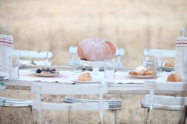 a white Thanksgiving tablescape with neutral pumpkins, a striped runner, striped plates