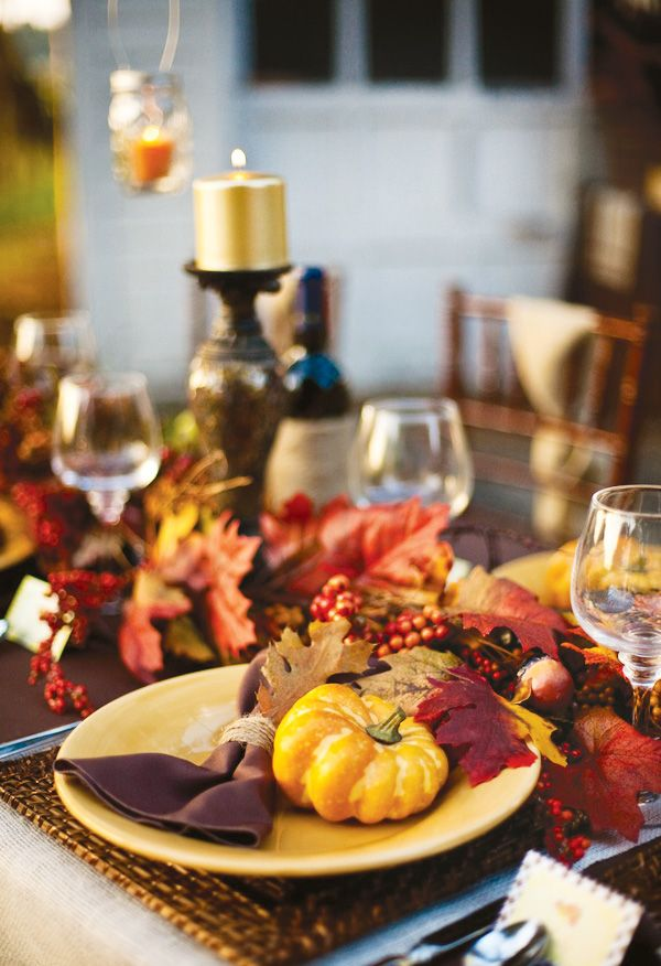 a bright Thanksgiving tablescape with bold fall leaves, pumpkins, bright napkins, berries and gold candles