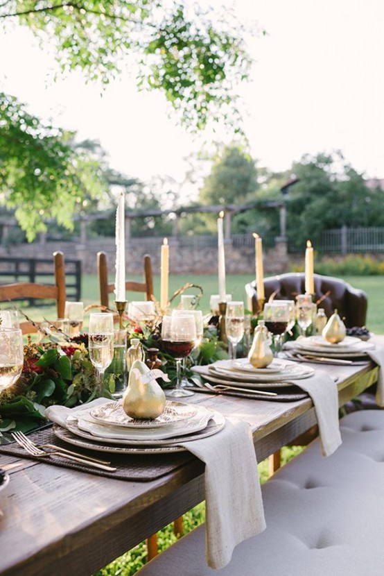 a Thanksgiving tablescape with a greenery and floral table runner, tall candles, gilded pears and printed plates