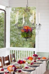 a colorful Thanksgiving tablescape with bright blooms, pumpkins and a bright floral decoration overheads
