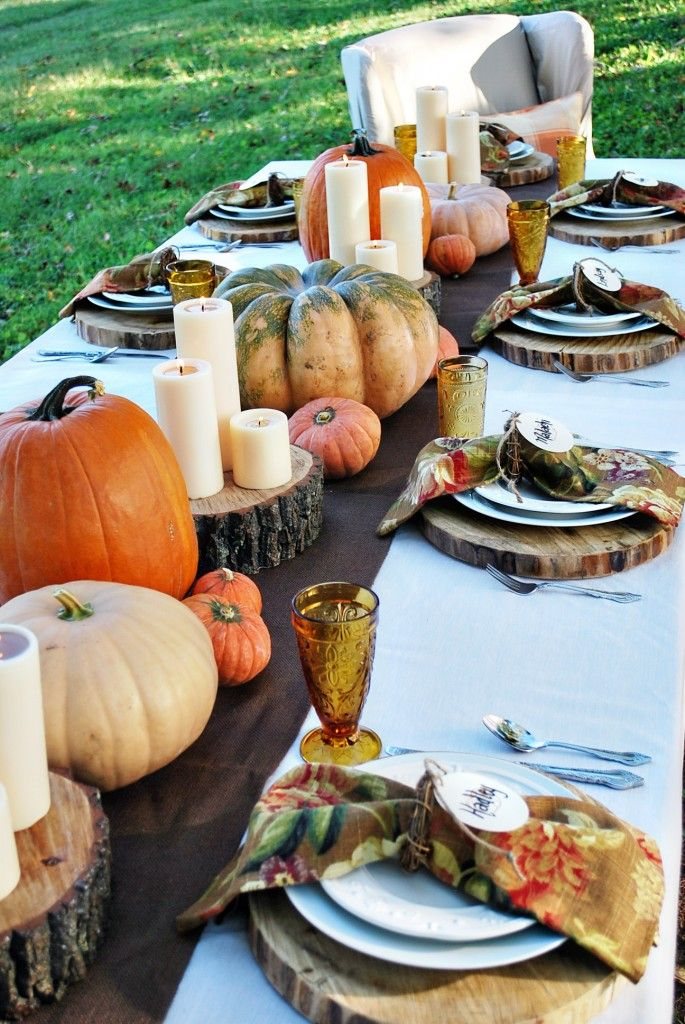 a modern rustic Thanksgiving table setting with a runner with wood slices, real pumpkins and pillar candles, colorful napkins and colored glasses