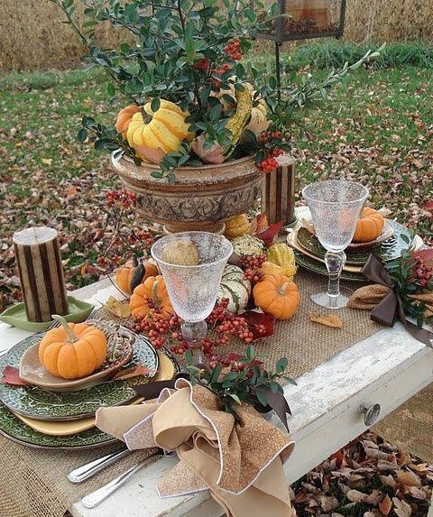 a vintage Thanksgiving tablescape with a large urn with greenery and veggies, a burlap table runner and some  pumpkins and berries on the table