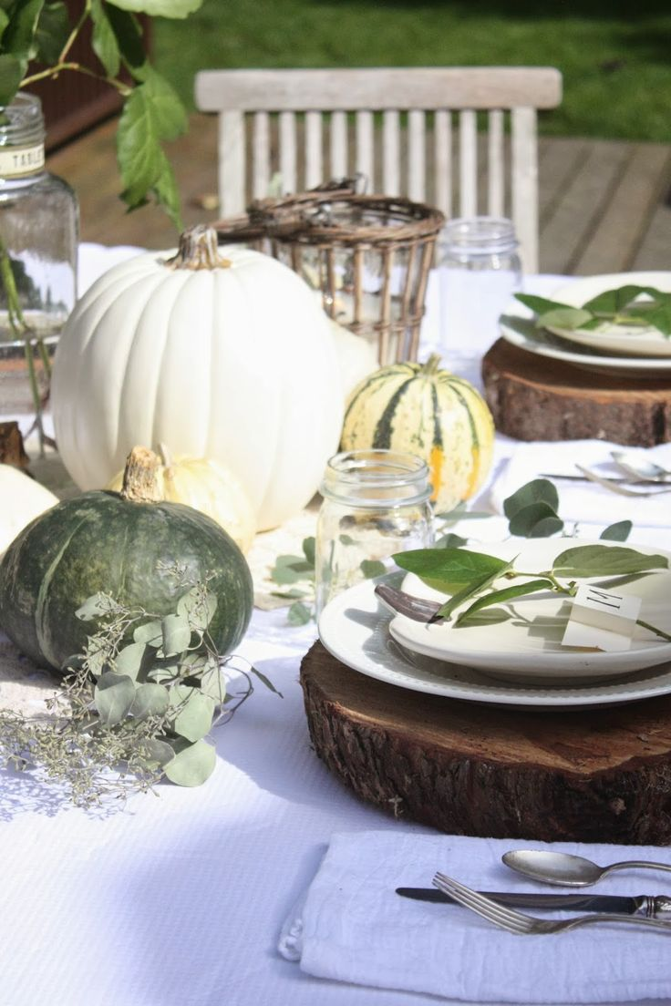 a nautral outdoor Thanksgiving table with white and green pumpkins, greenery and vine covered candleholders plus wood slices for placemats